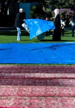 Makeda Mack helps to put down the tarp for Jummah Under the Sun Friday, Nov. 15, 2013. Photo by Benjamin Kamps / Xpress
