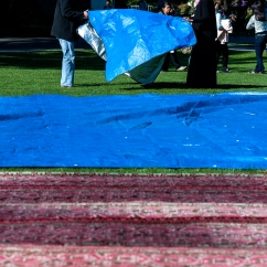Makeda Mack helps to put down the tarp for Jummah Under the Sun Friday, Nov. 15, 2013. Photo by Benjamin Kamps / Xpress